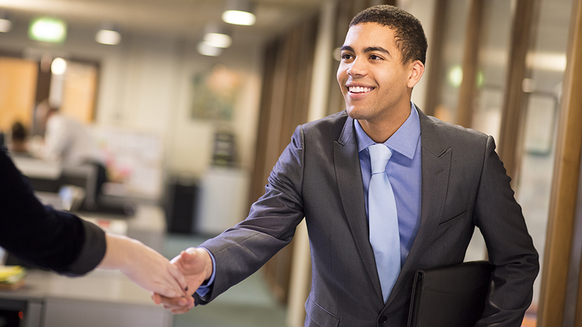 young man arrives at his interview , resume under his arm greeting his interviewer