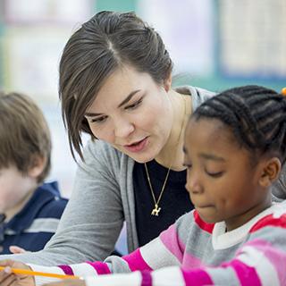 Elementary school teacher helping student
