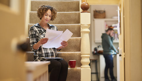 a woman sits on the stairs of her home and checks a bill that she has received using her digital tablet . She is smiling happily as she checks the amounts . In the background her partner is in the kitchen .