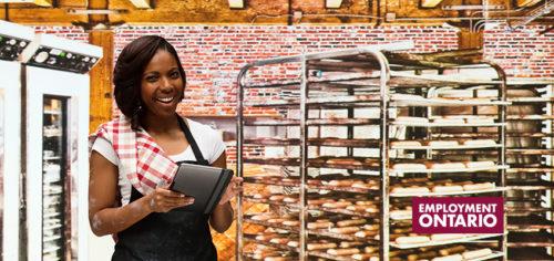 Smiling baker using tablet in bakery